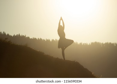 A silhouette of a young woman standing in vrikshasana, a tree pose of yoga, on sunrise