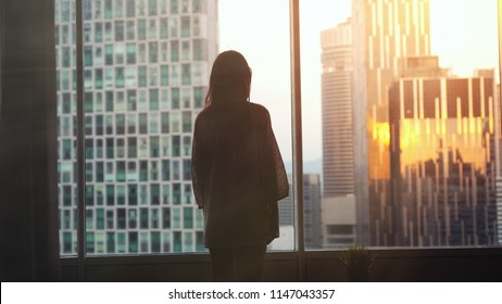 Silhouette of young woman stands by the big window and looking out her apartment on the city buildings