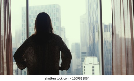 Silhouette of young woman stands by the panoramic window looking out apartment on the city buildings at home.