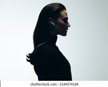 Silhouette of young woman in studio. Side view of female model wearing earphones.