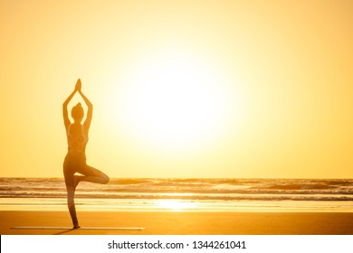 Silhouette of young woman in a stylish suit for yogi jumpsuit doing yoga on the beach in pose copy space