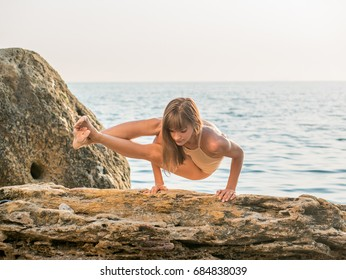 Silhouette of young woman in swimsuit practicing yoga at amazing sunrise. Fitness, sport, yoga and healthy lifestyle concept. Girl doing a bridge and asanas on rock in sea.