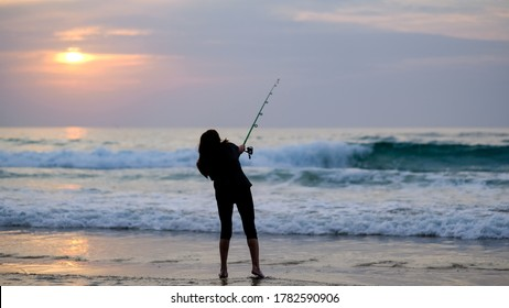 A silhouette of a young woman that throws her fishing rod towards the ocean during a beautiful sunset, Tel Aviv, Israel.