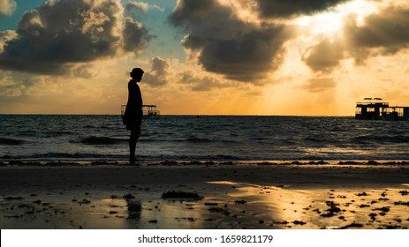 Silhouette of a young woman walking along the beach with a gorgeous golden sunrise on a beautiful beach in Joao Pessoa, Brazil.
