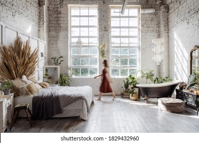 Silhouette of young woman walking at home with interior design in bohemian style against loft brick wall with large windows. Dreamy female standing between cozy bed in bedroom and bathroom bath