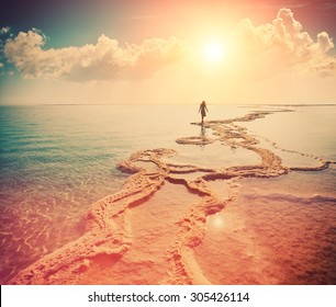 Silhouette of young woman walking on Dead Sea at sunrise