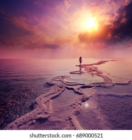 Silhouette of young woman walking on Dead Sea with dramatic sunset sky