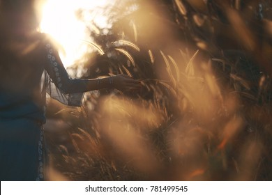 silhouette of young woman walking on a field sunset time