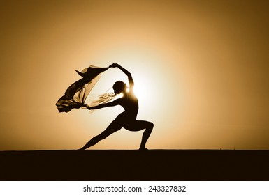 Silhouette of a young woman in a warrior yoga pose at sunset