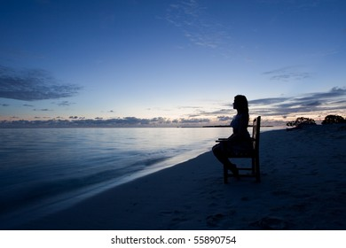 Silhouette of a young woman watching the ocean during nightfall