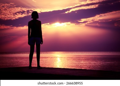 Silhouette of Young Woman Watching Sea Sunset. Breathtaking Nature Background. Toned Photo with Copy Space.