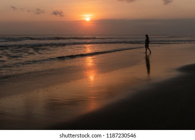 Silhouette of young woman watching sunset on the beach in canggu Bali