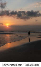 silhouette of a young woman watching sunset on the beach in canggu Bali