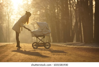 Silhouette of young woman in white coat and black hat with pompom standing elegant in sun on footpath and looking at child in baby stroller on backgroung on sunny winter park, childcare and love