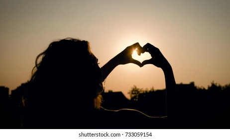 Silhouette of a young woman who is in the park zone, in nature, the girl shakes hands with a heart shape, she slowly moves her fingers, the sun is seen through her fingers
