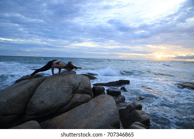 Silhouette  young women practicing yoga on the rocks. on the beach.with sky and beautiful light