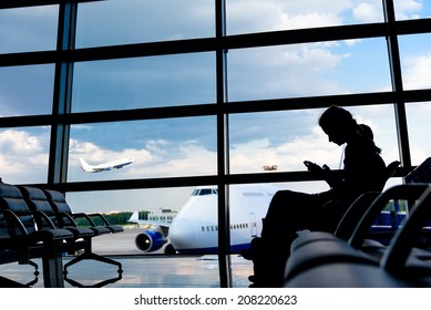Silhouette of young women with smartphone in airport. Jetliner in background.