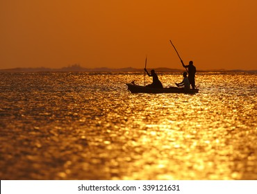 Silhouette of Zanzibar fishermen returning from fishing in the setting sun reflecting on the surface of the sea