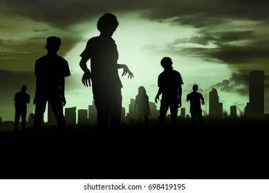 Silhouette of zombies walking over cemetery in night