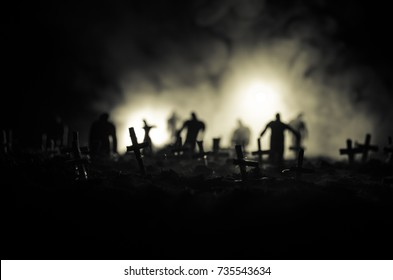 Silhouette of zombies walking over cemetery in night. Horror Halloween concept of group of zombies at night. Selective focus