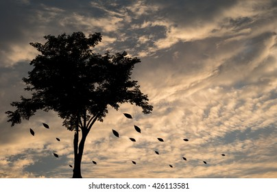Silhouette,blurry,art tone of a tree with fallen leaves on cloudy sky before rain background in the evening by mix picture in lonely emotion concept
