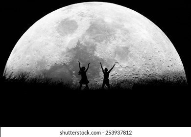 Silhouette,children playing jump on full moon background monochrome