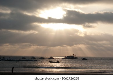 Silhouetted boats in front of setting sun in Salinas, Ecuador, with small silhouetted person walking beach in front