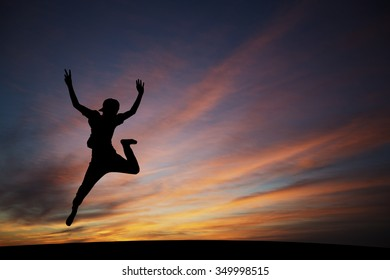 silhouetted boy jumping in sunset for fun