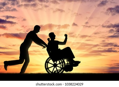 Silhouetted cheerful man having a disabled man in a wheelchair and his friend on a sunset background. Concept of people with disabilities in society