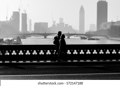 Silhouetted Couple Walking On Westminster Bridge London With Panoramic View Of Lambeth Bridge Behind Them Black And White Street Photography