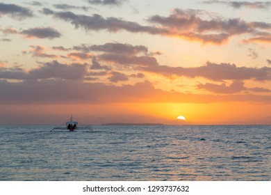 Silhouetted diving boat and beautiful tropical sunrise near Panglao island, Bohol, Philippines