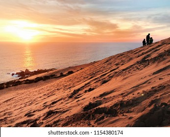 A silhouetted family climbs the Sand Dunes in Cóncon, Chile, near Valparaíso and Viña del Mar, as the sun sets over the Pacific