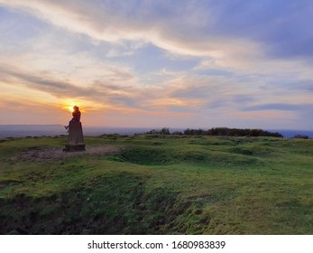 A silhouetted figure sits atop a monolith at the peak of an English hill. Their head is perfectly backlit by a yolk-orange setting sun, which lowers to the left of an overcast, purple-tinged sky. The