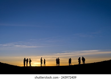 Silhouetted figures watch the sun set over Haleakala in Maui.