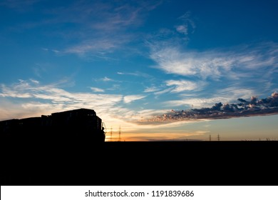 A silhouetted freight train on the Canadian prairie at sunset
