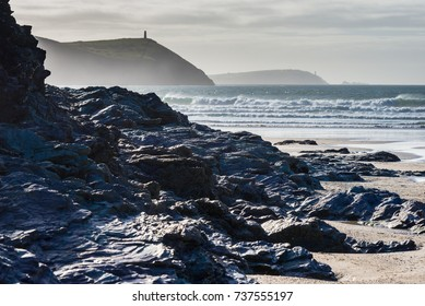 Silhouetted geology of Padstow Bay with surf and spray highlighted by late afternoon sun which appears to cause a haze across the bay