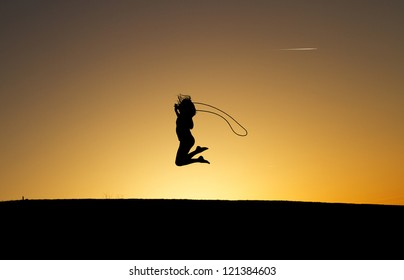 silhouetted girl rope skipping in sunset