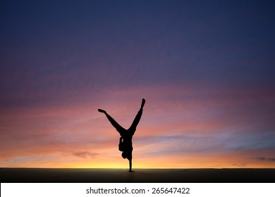 silhouetted gymnast dong one-handed handstand in sunset