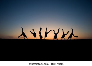 silhouetted gymnasts in sunset