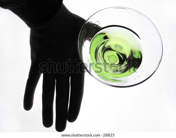 silhouetted hand holding a glass of martini, overhead shot.
