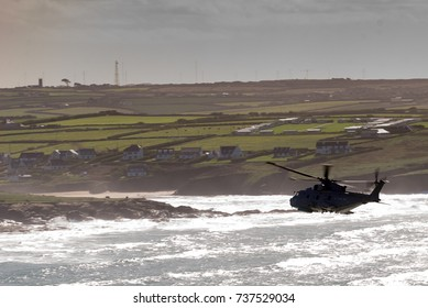 A silhouetted helicopter heads towards landfall with backlit fields and landmarks.  The sun catches the surf under the belly of the aircraft.