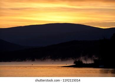Silhouetted hills around Shuswap Lake and colorful orange sky, British Columbia, Canada