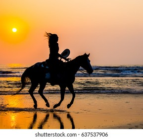 A silhouetted horse and rider running on the beach in the morning sun with hair and tail flying as all four feet are off the sand