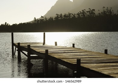 Silhouetted image of wooden dock in lake at sunset