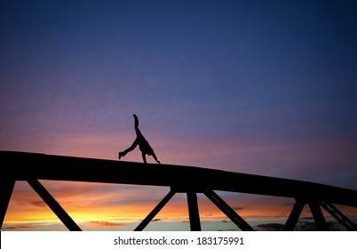 silhouetted man doing a cartwheel on steel bridge at sunset