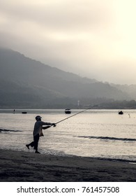 a silhouetted man holding fishing rod on beach during sunrise