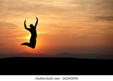 silhouetted man jumping in sunset