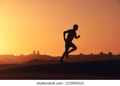 A silhouetted man runs across a dune at sunset with an exotic desert backdrop.