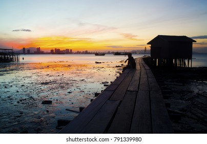Silhouetted Man Watches a Red Sunrise From the Clan Jetty - December 2017 - George Town, Penang, Malaysia