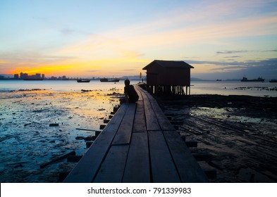 Silhouetted Man Watching Sunrise on the Pier - December 2017 - George Town, Penang, Malaysia